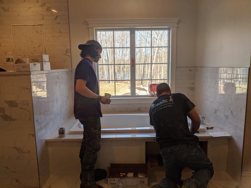 Tim and RJ installing a bathtub