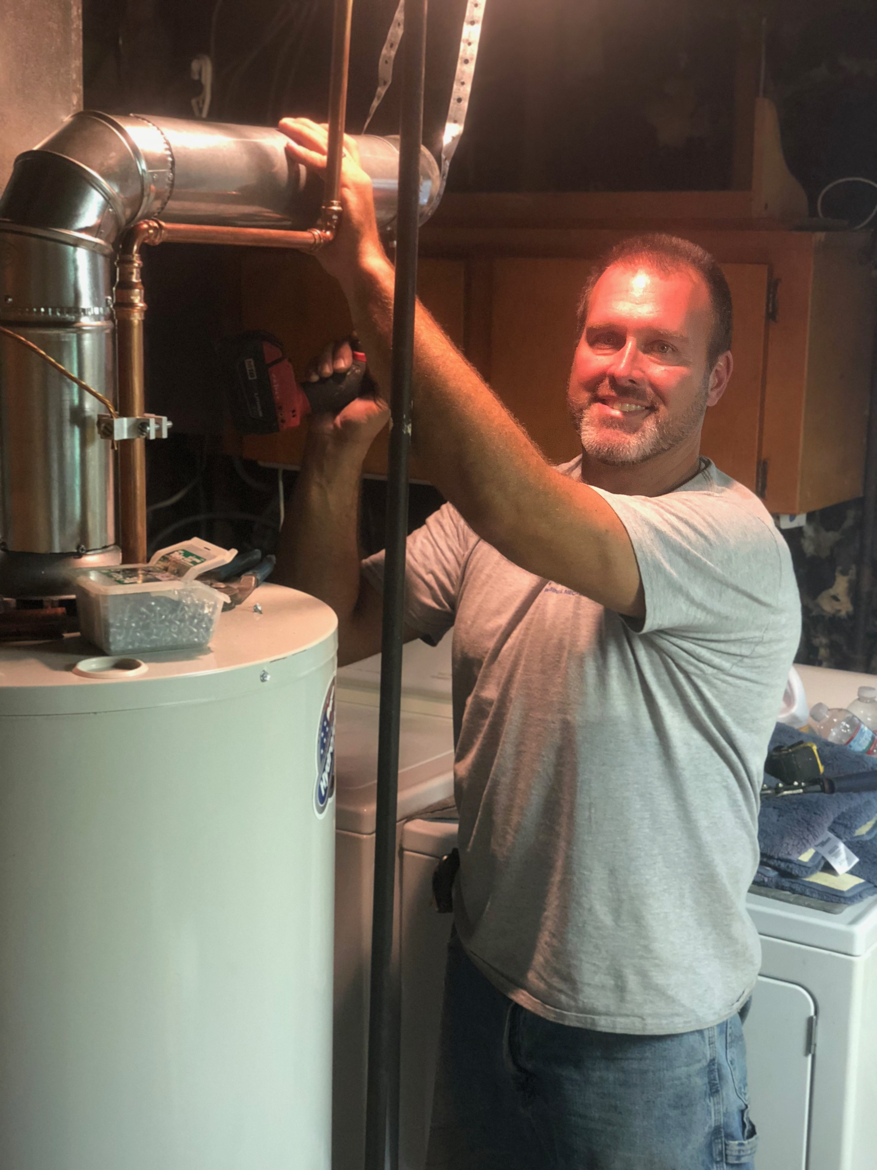 Tim installing flue pipe on water heater